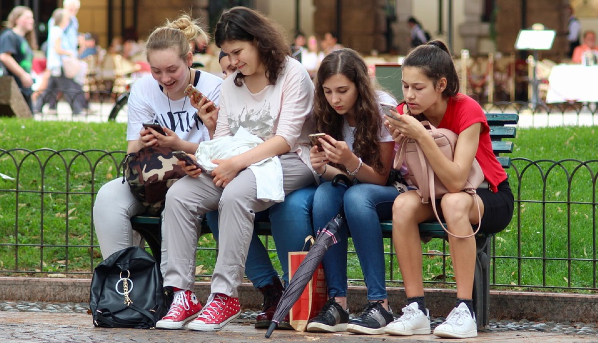 Group of teen girls on mobiles, likely browsing favourite Instagram influencers